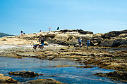Tourists look for sea life at China Cove, Point Lobos State Park, near Carmel Highlands, along Highway 1, Monterey County, California.