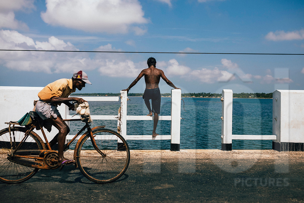 A fisherman looks out over the sea on the Jaffna Peninsula while an old man cycles accross the scene. Sri Lank, Asia
