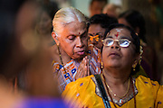 07 JANUARY 2014 - SINGAPORE:   People line up for blessings during afternoon pooja at Sri Veeramakaliamman Temple, a Hindu temple located in Little India in the southern part of Singapore. The Sri Veeramakaliamman Temple is dedicated to the Hindu goddess Kali, fierce embodiment of Shakti and the god Shiva's wife, Parvati. Kali has always been popular in Bengal, the birthplace of the labourers who built this temple in 1881. Images of Kali within the temple show her wearing a garland of skulls and ripping out the insides of her victims, and Kali sharing more peaceful family moments with her sons Ganesha and Murugan. The building is constructed in the style of South Indian Tamil temples common in Tamil Nadu as opposed to the style of Northeastern Indian Kali temples in Bengal. PHOTO BY JACK KURTZ