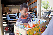 22 JUNE 2009 - PHOENIX, AZ: A client at the Cultural Cup food bank picks up his food box. The Cultural Cup has become a sort of community center. It started as a food bank and has since grown to include a clothing bank and free walk in clinic. The walk in clinic at the Cultural Cup Food Bank started two years ago when Cultural Cup founder Zarinah Awad wanted to expand the food bank's outreach and provide basic medical care for the people who use the food bank. The clinic sees, on average, 7 - 11 patients a week. Awad said that as the economy has worsened since the clinic opened and demand has steadily increased. She attributes the growth to people losing their jobs and health insurance. The clinic is staffed by volunteers both in the office and medical staff. Adults are seen every Saturday. Children are seen one Saturday a month, when a pediatrician comes in. Awad, a Moslem, said the food bank and clinic are rooted in the Moslem tradition of Zakat or Alms Giving, the giving of a small percentage of one's income to charity which is one of the Five Pillars of Islam.   PHOTO BY JACK KURTZ