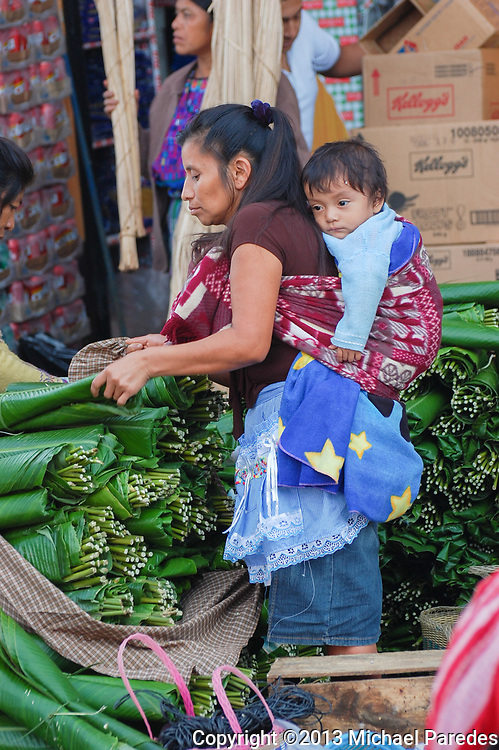A baby relaxes on his mother's back at a local market in Antigua, Guatemala