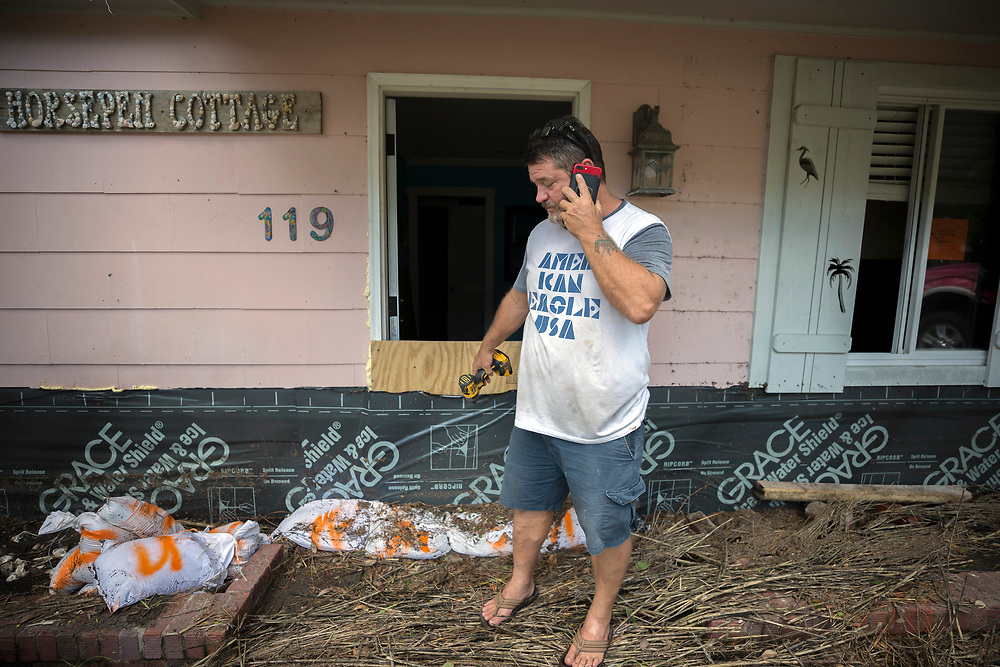 Joey Spalding talks to friends near his front door, Tuesday, Sept., 12, 2017, on Tybee Island, Ga., while cleaning up after Tropical Storm Irma flooded his neighborhood yesterday. (AP Photo/Stephen B. Morton)