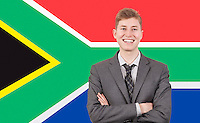 Young businessman with arms crossed over South African flag