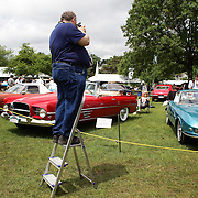 A man takes pictures from a ladder at the Greenwich Concours d'Elegance Festival of Speed and Style featuring great classic vintage cars. Roger Sherman Baldwin Park, Greenwich, Connecticut, USA.  2nd June 2012. Photo Tim Clayton