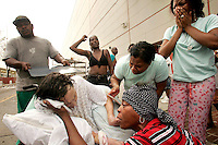 Dorothy Divic, 89, is surrounded by onlookers who are trying to keep her alive on a street outside the New Orleans Convention Center September 1, 2005. Several people among the thousands of stranded hurricane evacuees have died while waiting outside the building, with no sign of imminent help on the way.