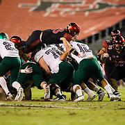 22 September 2018: San Diego State Aztecs safety Parker Baldwin (33) jumps over the offensive line to tackle Eastern Michigan Eagles quarterback Tyler Wiegers (12) on a fourth and one play in the first quarter. The San Diego State Aztecs beat the Eastern Michigan Eagles 23-20 in over time at SDCCU Stadium in San Diego, California.