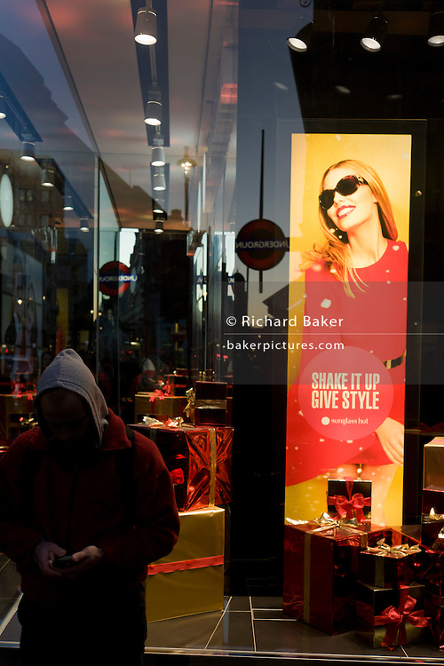 A man wearing a hoodie uses a smartphones beneath a poster girl for Burberry sunglasses they call Eyewear, in a sunlit London street.