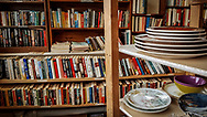 Piles of dishes and used books lie on shelves at Worth A Second Look (WASL), a used furniture store that is part of The Working Centre, in 2017 at Kitchener, Ontario. WASL is a social enterprise project.
