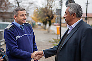 Activist and Roma local councilor Gheorghe Tudor discussing with a local police officer in  front of the town hall in Filipestii de Targ to which Marginenii de Jos belongs. Tudor who has been an activist for social change during the past 25 years, becoming the first elected Roma representative in the local council of Marginenii de Jos in 1992.