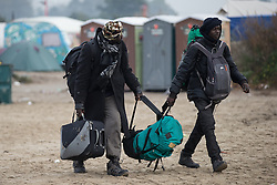 © Licensed to London News Pictures . 24/10/2016 . Calais , France . People including children leaving the Jungle migrant camp in Calais , Northern France , with their parents , on the day of a planned eviction and start of the destruction of the camp . Photo credit: Joel Goodman/LNP