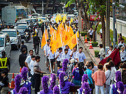 18 NOVEMBER 2015 - BANGKOK, THAILAND:  Thai high school students carry Buddhist flags in the procession marking the start of the Wat Saket annual temple fair. Wat Saket is on a man-made hill in the historic section of Bangkok. The temple has golden spire that is 260 feet high which was the highest point in Bangkok for more than 100 years. The temple construction began in the 1800s in the reign of King Rama III and was completed in the reign of King Rama IV. The annual temple fair is held on the 12th lunar month, for nine days around the November full moon. During the fair a red cloth (reminiscent of a monk's robe) is placed around the Golden Mount while the temple grounds hosts Thai traditional theatre, food stalls and traditional shows.     PHOTO BY JACK KURTZ