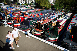 © Licensed to London News Pictures. 06/05/2018. London, UK. A coupe enjoy a walk along the canal tow path on day two of the Canalway Cavalcade festival takes place in Little Venice, West London on Sunday,  May 6th 2018. Inland Waterways Association's annual gathering of canal boats brings around 130 decorated boats together in Little Venice's canals on May bank holiday weekend. Photo credit: Ben Cawthra/LNP