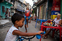 Youths play in Complexo da Mare, Rio de Janeiro, Brazil, on Saturday, April 27, 2013. Complexo da Mare, is a complex of 16 communities, in the north zone of Rio de Janeiro. It is the largest complex of favelas with 130,000 residents. It is targeted for pacification as the city prepares for the 2014 World Cup and the 2016 Olympics. Four factions run the complex -  three drug gangs and the militia. The rival gangs fight for control of the drug trade. Although crime is low in the favelas by rule  of law enforced by the gangs, cross-fire shootings and gang violence is often high. Neighborhood associations are an integral part of community development within Mare, making up for a lack of government assistance.