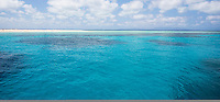 View of the Coral Sea on a sunny day with clouds in the sky, off the coast of tropical north Queensland, Australia