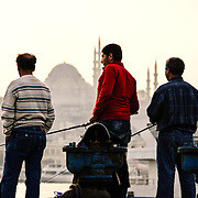 Three fishermen cast their lines in the Golden Horn on the waterfront near the Karakoy Fish Market in Istanbul near the Galata Bridge. In the disance is the Suleymaniye Mosque.