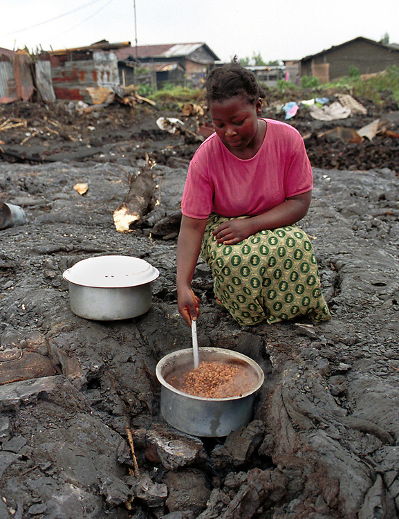 A resourceful woman uses a hot fissure in the lava to boil her beans. The lava is stil hot, amost two weeks after the eruption of  Nyiragongo volcano on the 17th January 2002 which totally destrpyed the city of 400,000 people and claimed 50 lives..