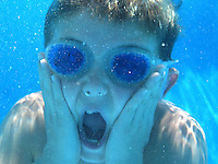 Kids play underwater at an outdoor pool