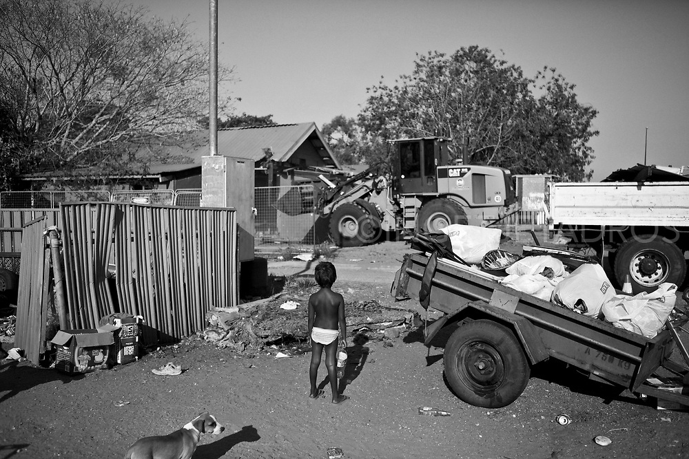 Five-year-old Meah stands outside her family home<br />watching a bulldozer demolishing the Mallingbarr<br />(Kennedy Hill) community&rsquo;s office. Only seven houses<br />remain in the community, one of dozens slated for<br />closure by Western Australia. Broome, Western Australia