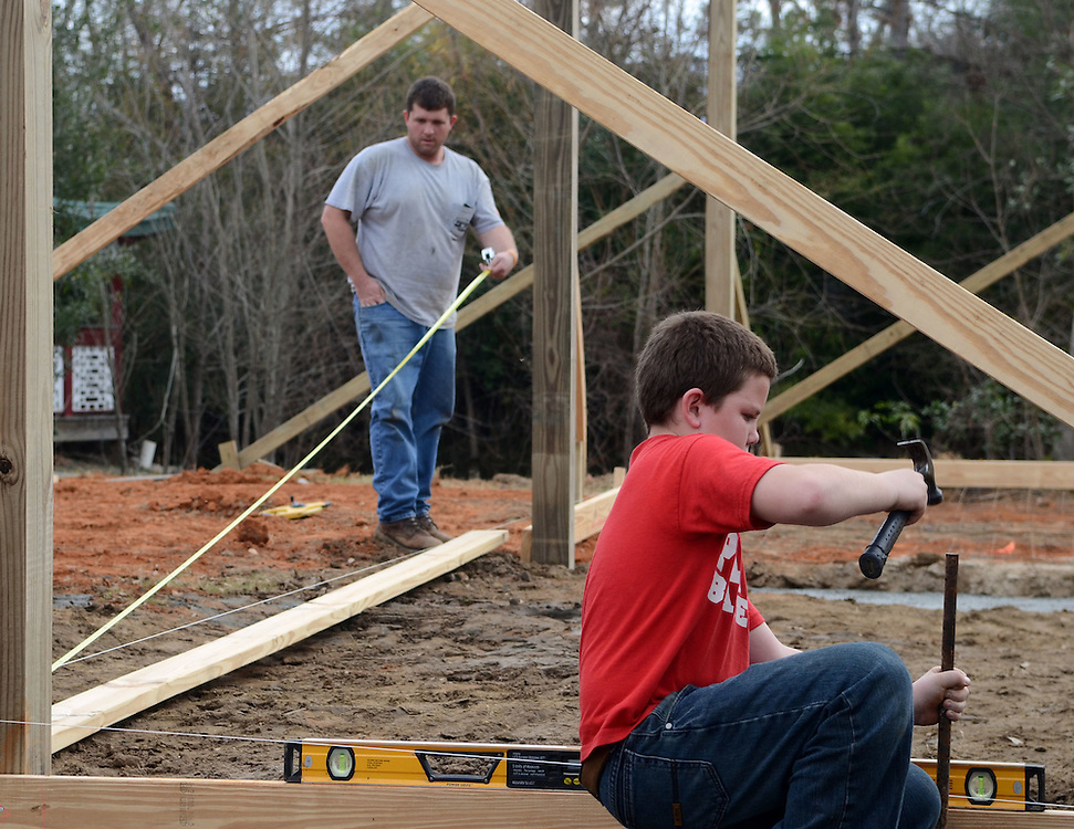 Josh Young, 11, works on Monday while helping his father Jody build two new pavilions at the Hattiesburg Zoo. The zoo is closed this week for construction. Bryant Hawkins/The Hattiesburg American