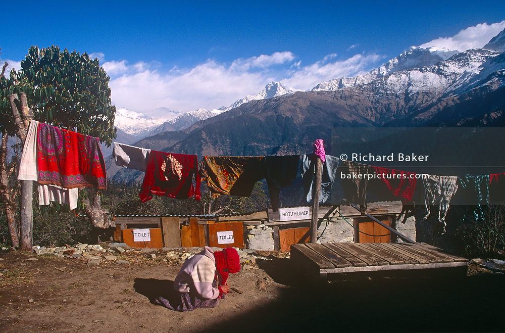A child plays outside its home with the backdrop of snow-tipped Himalayan mountain peaks, a location also serving as a trekkers' rest house with hot, solar-powered showers, on 10th November 1995, in Ghorepani, Himalayas, Nepal,