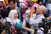 05 JANUARY 2014 - BANGKOK, THAILAND:  SUTHEP THAUGSUBAND, leader of the anti-government movement, greets the crowd while a Thai Muslim woman waits to see him during a march through Bangkok Sunday. Suthep is a former Deputy Prime Minister and member of the opposition Democrat Party who resigned to organize the protests against the Pheu Thai government.  He led the protestors on a march through the Chinatown district of Bangkok. Tens of thousands of people waving Thai flags and blowing whistles gridlocked what was already one of the most congested parts of the city. The march was intended to be a warm up to their plan by protestors to completely shut down Bangkok starting Jan. 13.    PHOTO BY JACK KURTZ