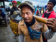 03 AUGUST 2017 - KUTA, BALI, INDONESIA: Men wait to weigh the catch fish caught by a trawler and offloaded by a tender on Jimbrana Beach in Kuta. The beach is close to the airport and a short drive from other beaches in southeast Bali. Jimbrana was originally a fishing village with a busy local market. About 25 years ago, developers started building restaurants and hotels along the beach and land prices are rising. The new emphasis on tourism is changing the nature of the area but the fishermen are still busy very early in the morning.     PHOTO BY JACK KURTZ