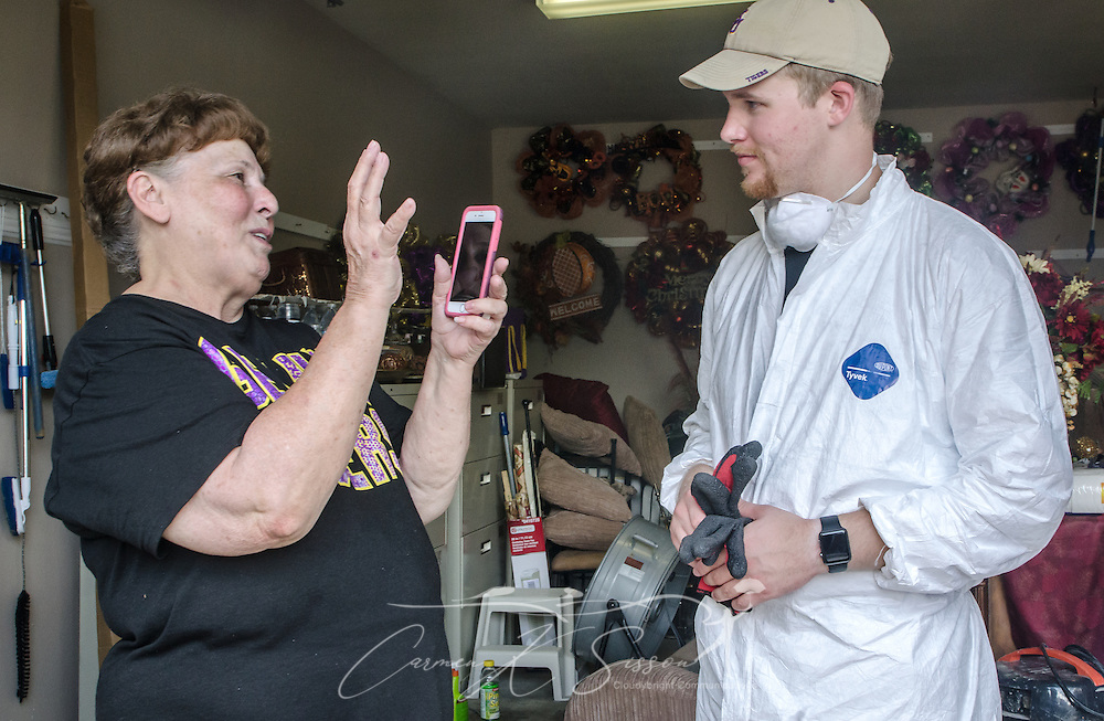 Homeowner Paulette LaCombe, a member of Immaculate Conception Church in Baton Rouge, shares a funny story with LSU student Cullen McDaniel, Sept. 3, 2016, in Denham Springs, La. McDaniel, a member of Jefferson Baptist Church in Baton Rouge, was among 450 students from six states who gathered in Baton Rouge and nearby communities on Labor Day weekend to help survivors of the mid-August flood. LaCombe said she had spent the week crying, but the students gave her hope and made her smile. (Photo by Carmen K. Sisson)