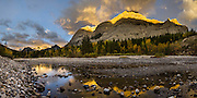Sunrise spotlights Mount Kidd and reflects in Kananaskis River in the Kananaskis Range of the Canadian Rockies, Alberta, Canada. Access the Mt Kidd Interpretive Trail from the huge Mt Kidd RV Park. Kananaskis Country is a park system west of Calgary.  This panorama was stitched from 11 overlapping photos.