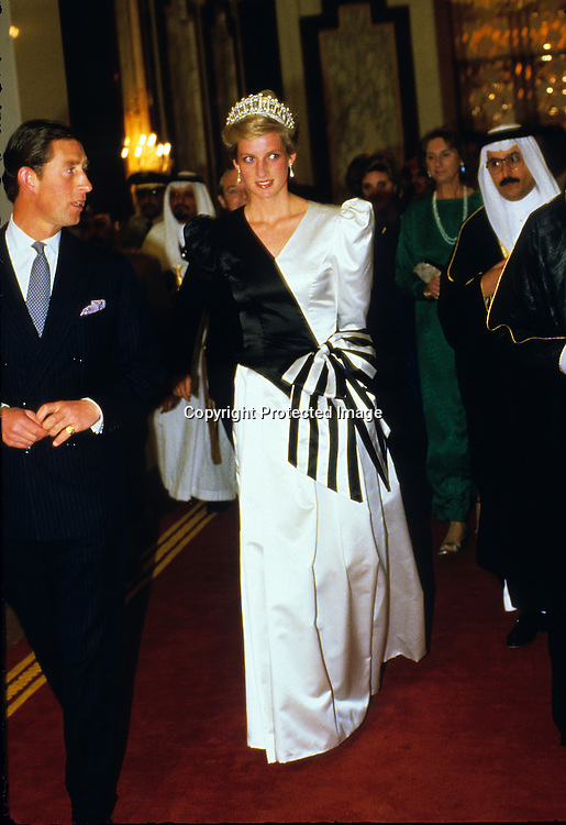 Diana, Princess of Wales, wearing an evening dress designed by the Emmanuels and accompanied by Prince Charles, Prince of Wales, arrives at a dinner given by the Crown Prince in Saudi Arabia on November 17, 1986.<br />