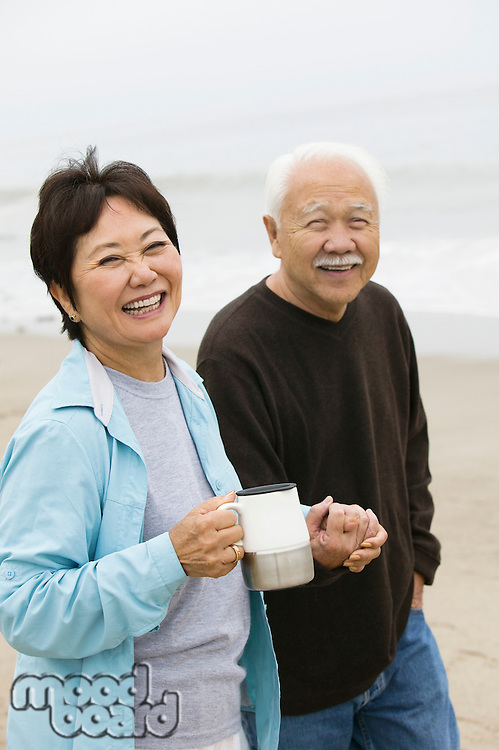 Senior couple on beach holding hands and looking at camera