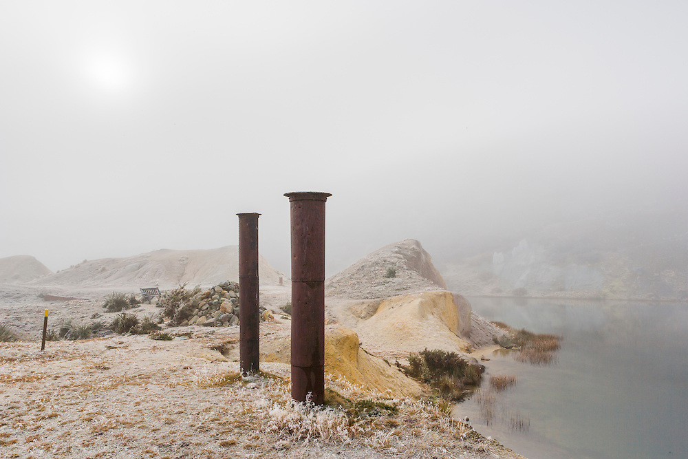 Two chimney stacks beside Blue lake in the mist, relics from gold mining days.