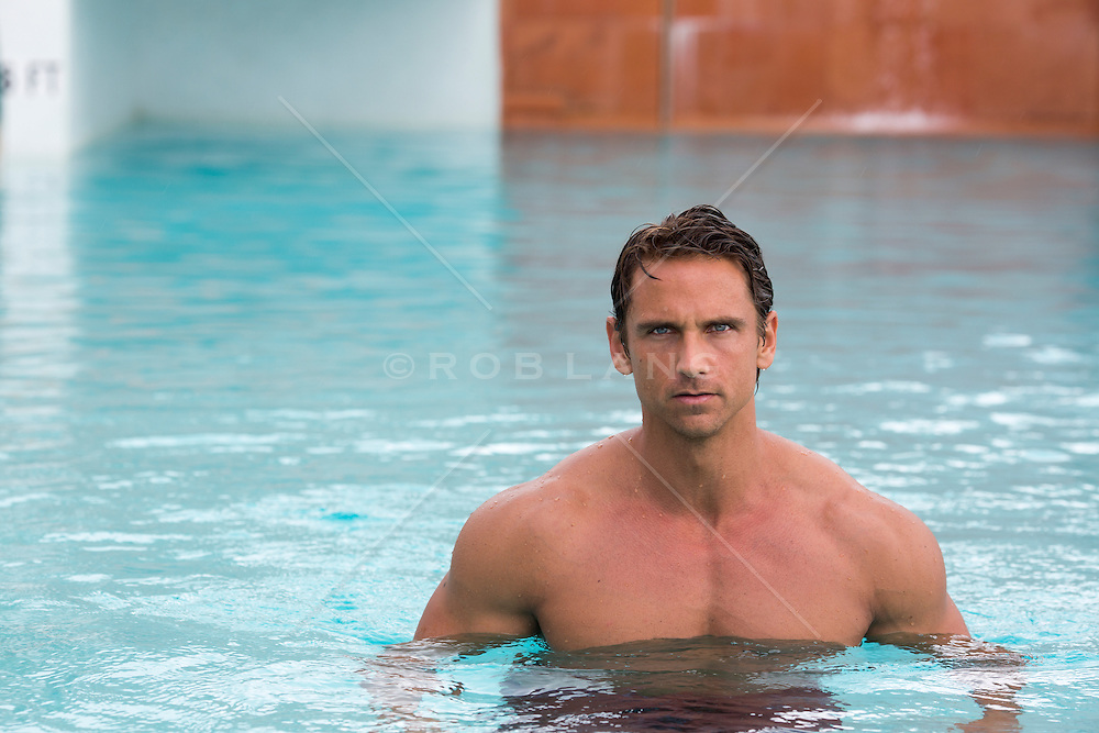 sexy man standing in shallow water in a swimming pool at an outdoor spa