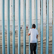 Two friends, one on the Mexican side, the other on the American side of the border, trying to communicate with each others through the phone as the American border guards don't allow people to get very near to the wall. Playas de Tijuana. Life and everyday scenes at the beach of Tijuana. The beginning of the infamous wall between Mexico and United States of America, that starts in the Pacific Ocean and goes all the way for more than 1,000 km until Ciudad Juarez / El Paso border, in Texas