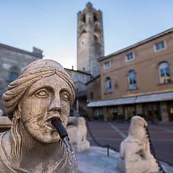 The Contarini fountain in the central square Piazza Vecchia in Bergamo, Italy. On the background, the Palazzo del Podestà and the Campanone. The Fountain was created with Zandobbio marble in 1780