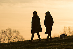 © Licensed to London News Pictures. 28/01/2015. London, UK. Two women walk along Parliament Hill during a warm orange sunrise and cold weather this morning. Photo credit : Vickie Flores/LNP
