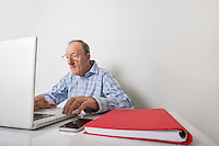 Senior businessman using laptop with book binder and cell phone on office desk
