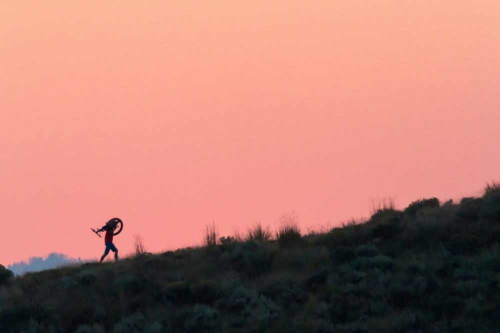 Andrew Whiteford carries his bike up hill under and through the light of sunset.