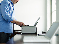 Middle-aged man using printer side view mid section