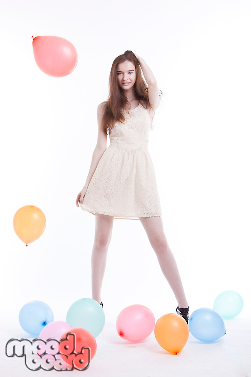 Beautiful young woman in dress with balloons on floor against white background