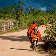 Cheeky young novice monk smoking cigarette on bicycle (Vang Vieng, Laos - Nov. 2008) (Image ID: 081122-1447111a)