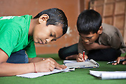 Two Nepalese young boys practice writing in a class room in the Voice of Children rehabilitation center in Kathmandu, Nepal.  The not-for-profit organisation supports street children and those who are at risk of sexual abuse through educational and vocational training opportunities, health services and psychosocial counseling.