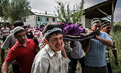 Uzbek men carry the body of a woman killed in the ethnic clashes, during the funeral ceremony in Osh, Kyrgyzstan, 15 June 2010. According to media reports 176 people were killed and 1700 wounded during the ethnic clashes in Kyrgyzstan during past days.