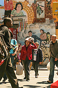 People passing by a mural painting in Chinatown, in New York.