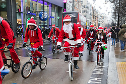 © Licensed to London News Pictures. 15/12/2018. London, UK.  People dressed as Father Christmas taking part in a fundraising Stanta Cycle event, cycle along Oxford Street, surprising shoppers this afternoon.  Photo credit: Vickie Flores/LNP