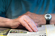 hands of an elderly man following the lines reading the newspaper