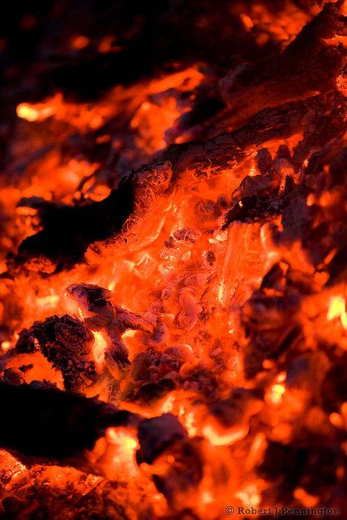 Burning hot coals and ash radiating heat with a narrow focus depth of field.