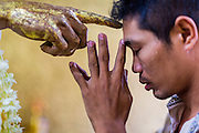04 JUNE 2014 - YANGON, YANGON REGION, MYANMAR: A man touches his forehead to a deity for good luck in Botataung Paya (Pagoda) in Yangon, Myanmar (Rangoon, Burma). Botataung is one of the most famous pagodas in Yangon with maze like interior of gold leaf covered walls. The pagoda houses a hair from the Buddha and is one of the most sacred sites in Burma. Yangon, with a population of over five million, continues to be the country's largest city and the most important commercial center.     PHOTO BY JACK KURTZ