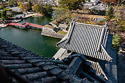 """Outward views from upper floors of Matsumoto Castle, built in 1614, in Matsumoto, Nagano Prefecture, Honshu, Japan. Matsumoto Castle is a """"hirajiro"""" - a castle built on plains rather than on a hill or mountain, in Matsumoto. Matsumotojo's main castle keep and its smaller, second donjon were built from 1592 to 1614, well-fortified as peace was not yet fully achieved at the time. In 1635, when military threats had ceased, a third, barely defended turret and another for moon viewing were added to the castle. Interesting features of the castle include steep wooden stairs, openings to drop stones onto invaders, openings for archers, as well as an observation deck at the top, sixth floor of the main keep with views over the Matsumoto city."""
