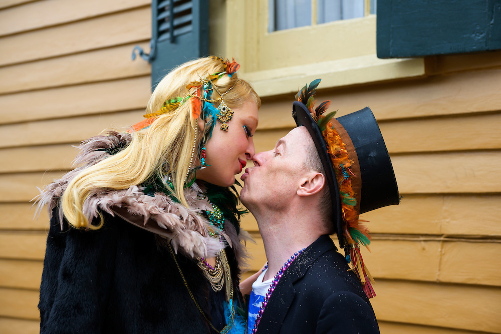 A man and woman from England kiss on a quiet street corner in the French Quarter of New Orleans during Mardi Gras 2013.