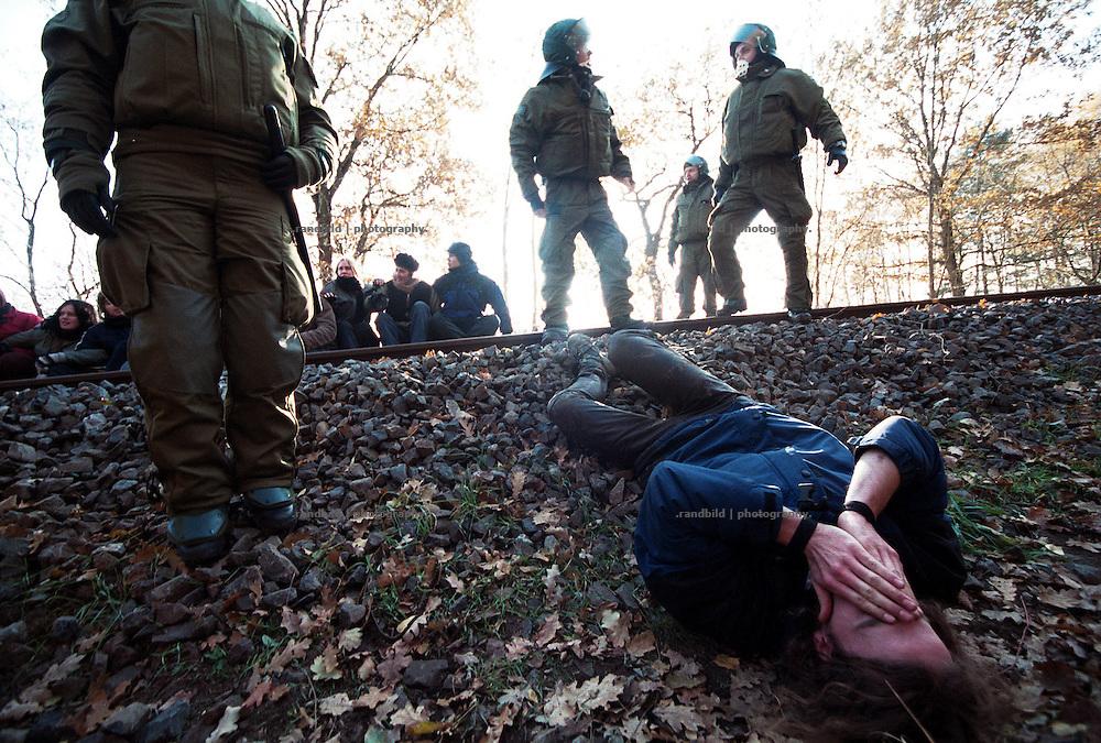 Ein Atomkraftgegner, der versuchte die Gleise (hinten) für eine Blockade eines Atomtransportes zu erreichen, liegt von der Polizei niedergeschlagen kopfüber auf dem Gleisschotter.
